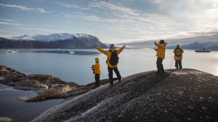 Guides and passengers from Essential Greenland expedition cruise stand atop a rock, arms outstretched, with a view of the ocean and the arctic in front of them.