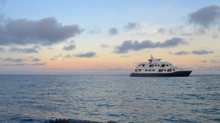 The 16-guest yacht of the Cormorant cruise navigates the horizon of the ocean during a pink sunset at the Galapagos islands