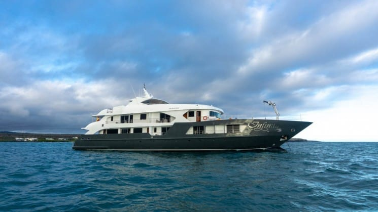 The 20-person yacht of Galapagos Infinity luxury cruises navigates open seas under blue sky with clouds at the Galapagos Islands