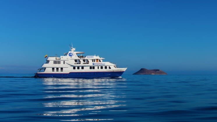 The Natural Paradise cruise ship traverses the horizon between a blue ocean and a blue sky at the Galapagos Islands.