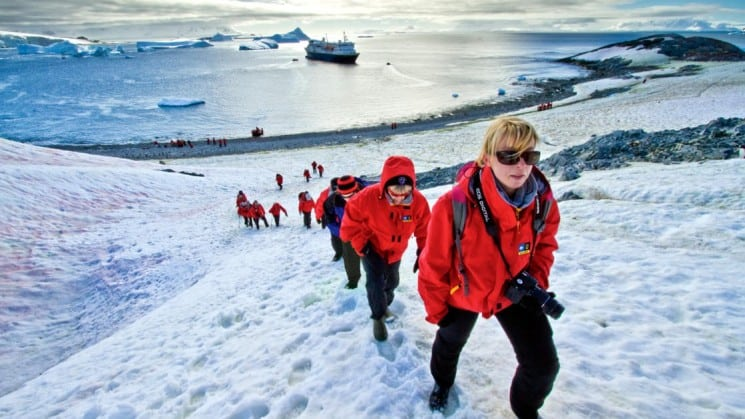 A group of people in red jackets hike up a snow-covered mountain with the ocean and national geographic ship in the background