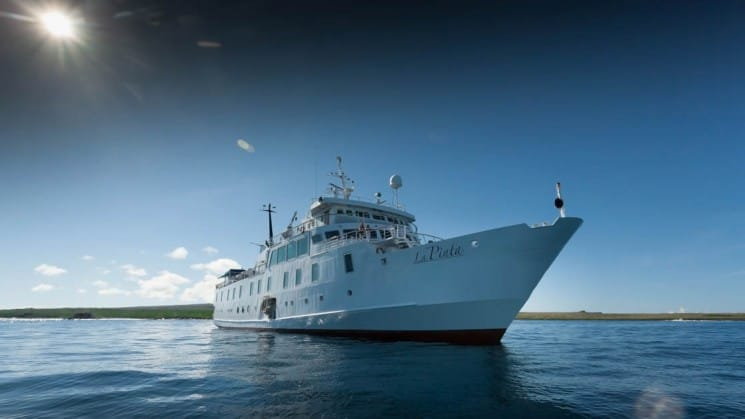 A white yacht anchored in calm seas, the La Pinta cruise ship accommodates 48 guests in 24 cabins with a sophisticated, upscale travel experience to the Galapagos Islands