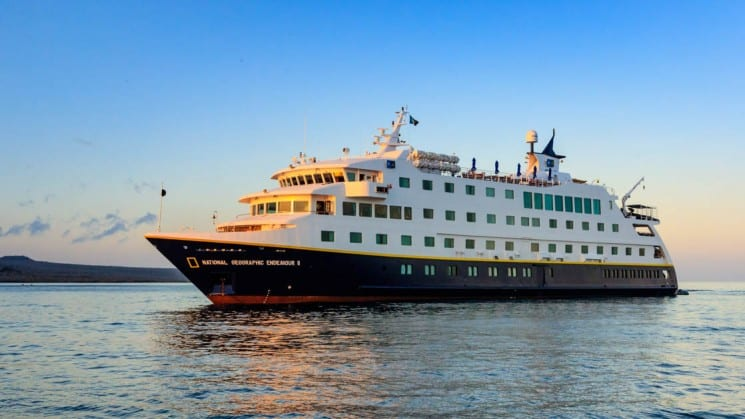 The 96-passenger National Geographic Endeavour II, a first-class expedition vessel, glides across calm waters on its way to the Galapagos Islands.
