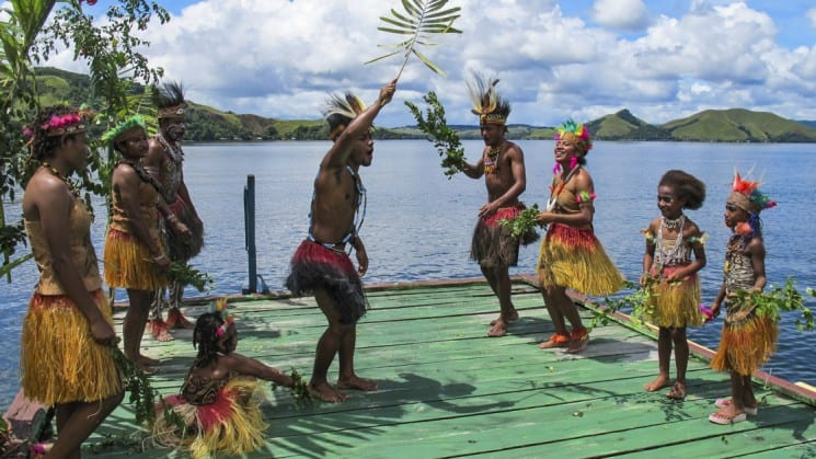 People wearing traditional clothing and headdresses dance on a pier overlooking the water in papua new guinea in the pacific islands