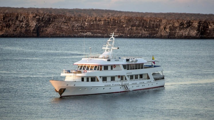 A luxury yacht, the Wildaid's Passion cuts across calm waters with the Galapagos islands in the background