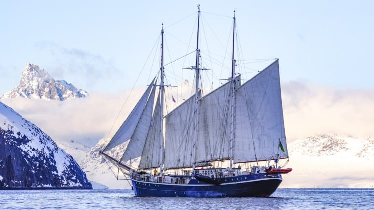 The masted Rembrandt van Rijn small sailing ship navigates the calm ocean in the arctic circle near spitsbergen