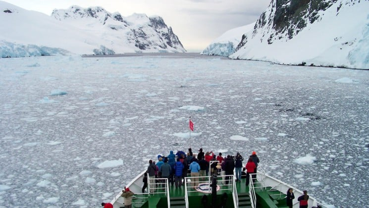 On an expedition to the Antarctic Circle, passengers crowd the ship's bow as they motor toward icebergs in the distance