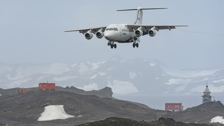 An airplane descends to land on King George Island in antarctica