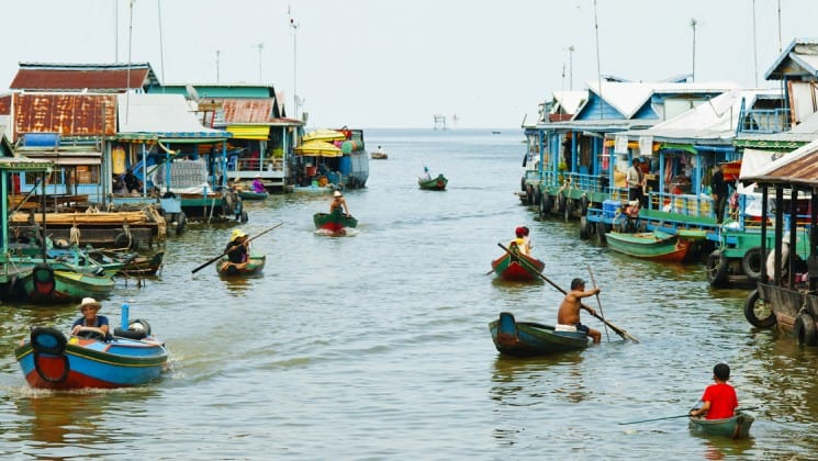 Two rows of people in canoes paddle down the Mekong River through a village in Cambodia