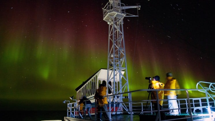 The aurora borealis or northern lights illuminate a dark sky with red and green hues, with the ship's deck in the foreground