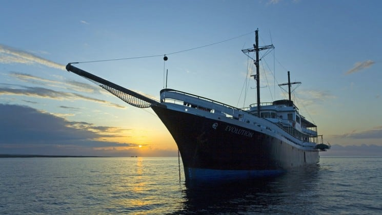 The evolution luxury cruise yacht cuts across still water at sunset near the Galapagos islands
