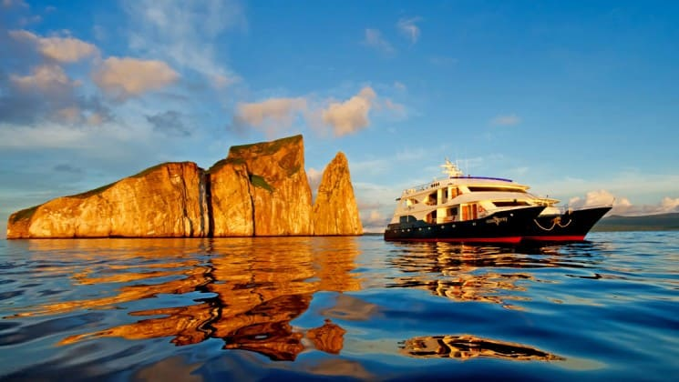Evening light illuminates rocks jutting out of the ocean at the galapagos islands, near the ocean spray luxury eco cruise