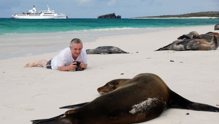 A passenger from the Legend Galapagos luxury cruise lies on his belly on the sand to capture a photo of a sunbathing sea lion.