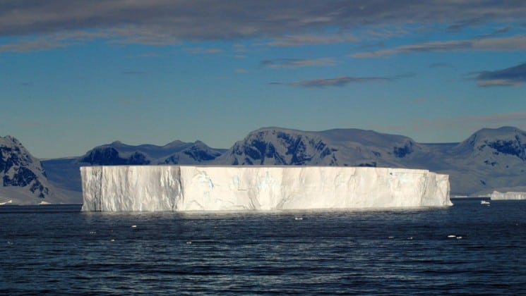 The cap of an iceberg rises above the sea water in antarctica as part of the polar circle cruise