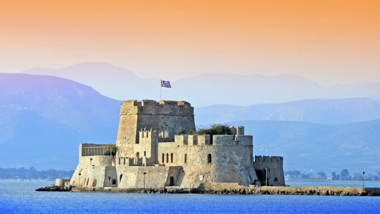 A fortress on an island in nafplion, greece, at sunset