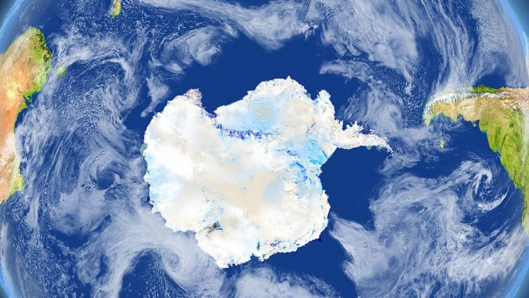 A satellite image of the white continent, antarctica, surrounded by blue ocean and green land with clouds swirling all around