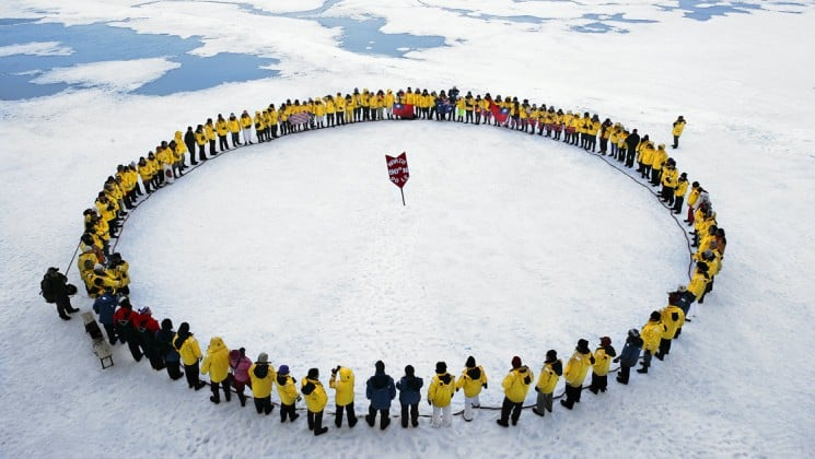 People on an expedition stand in a large circle around the North Pole, marked by a red flag at 90 degrees north