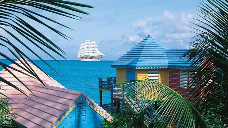 The small ship sea cloud sails on the tropical caribbean ocean with palm trees and yellow houses in the foreground