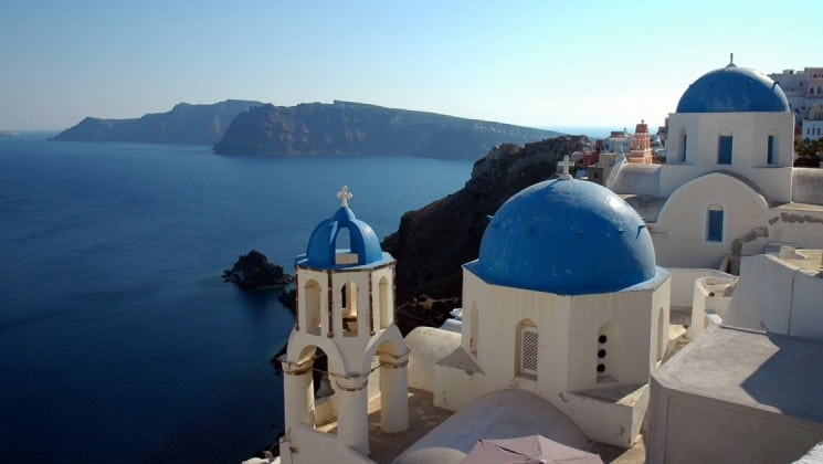 A view overlooking the mediterranean ocean in Greece, with white buildings and blue roofs of santorini in the foreground