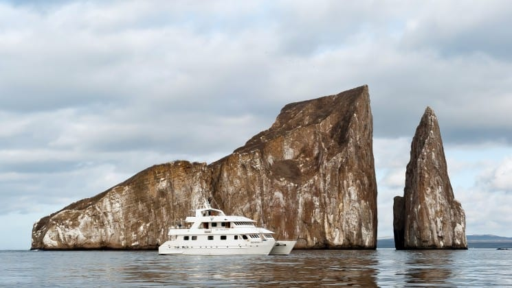 The seaman journey cruise, a luxury yacht, motors across a calm ocean in front of rocks jutting out of the water at the Galapagos islands