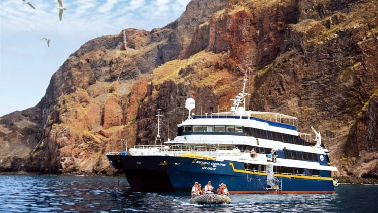 A zodiac takes passengers from the National Geographic Islander cruise ship to the Galapagos Islands, also pictured in the background with birds flying in the sky.
