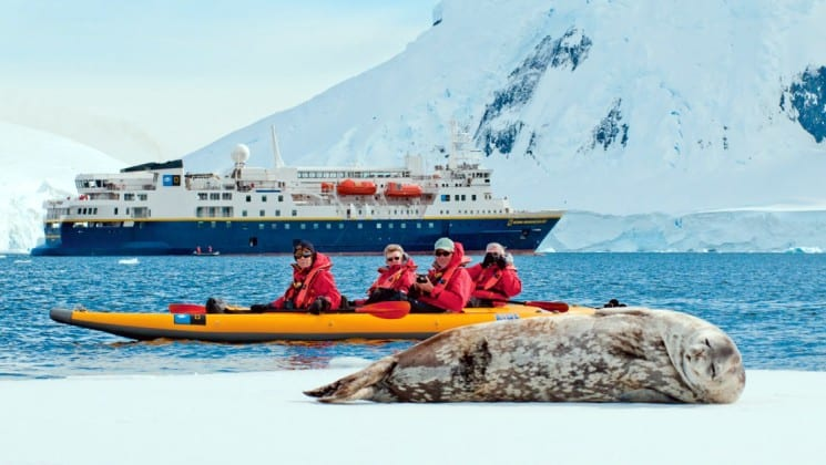 A seal lounges on the ice while a kayak full of passengers from the National Geographic voyage passes by