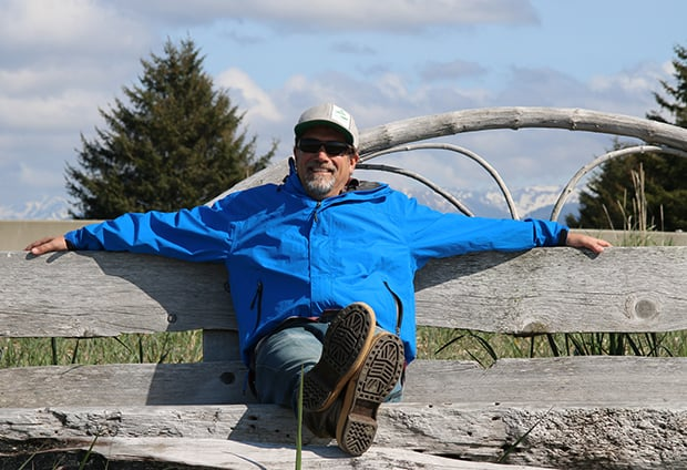 AdventureSmith founder Todd Smith relaxing on a wooden bench in Gustavus Alaska.