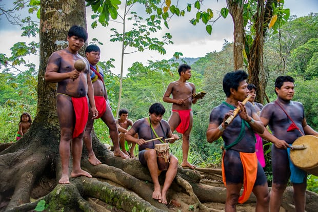 Embera people in traditional clothing playing traditional instruments in the costa rica jungle
