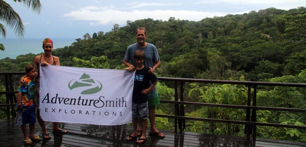 Costa Rican traveling family holding the Adventuresmith Explorations flag on the deck overlooking jungle and ocean in Lapa Rios.