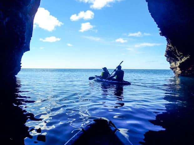 Couple kayaking through a large cave off the Galapagos Islands.