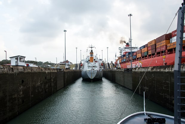 Small ship cruise in the locks of the Panama Canal with a another vessel and cargo ship in the locks.