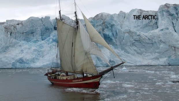 A small ship with its sails down in front of an iceberg