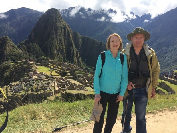Happy couple on a hiking trail overlooking the ancient ruin of Machu Picchu in Peru.