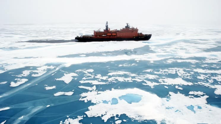 The powerful ship Fifty Years of Victory breaks through ice in the ocean in the arctic, heading toward the north pole
