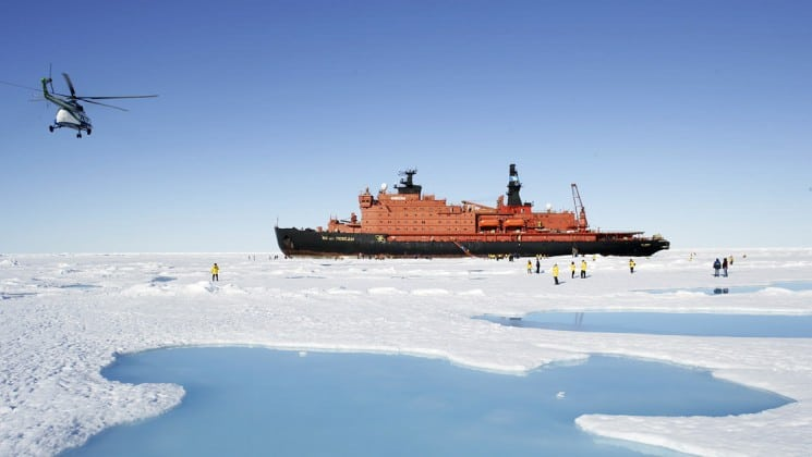 A landscape portrait of the ship fifty years of victory cutting through a field of ice in the arctic, headed toward the north pole, while a helicopter flies in the distance