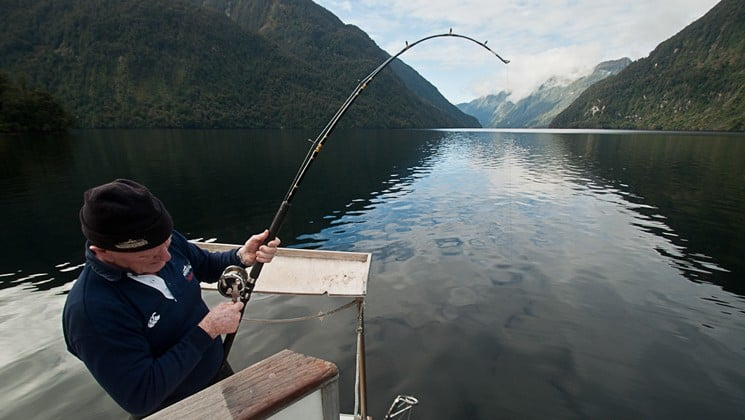 A person holds a fishing pole over the water in New Zealand's fiordland