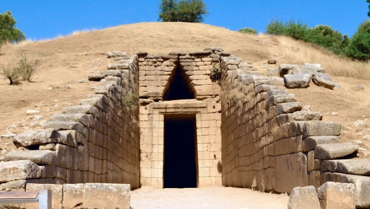 an ancient greek doorway is built into a hillside, in the archealogical site of mycenae