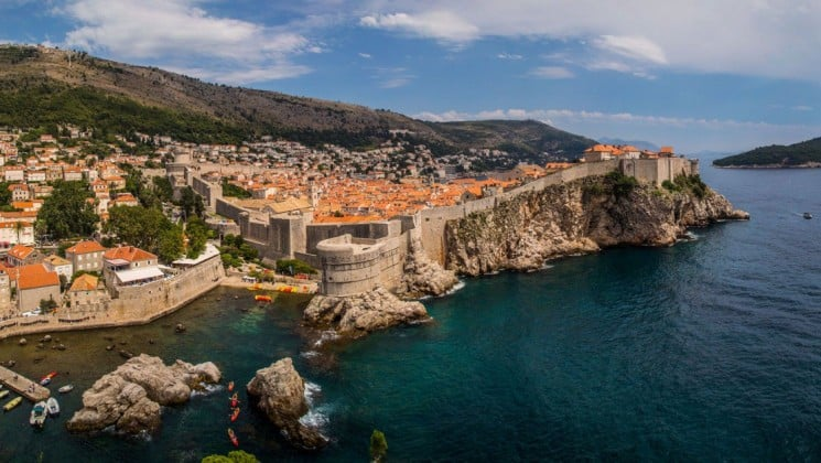 The dalmation coast in croatia with sheer cliffs plunging into the sea and towns with red-tiled roofs nestled into green hillsides