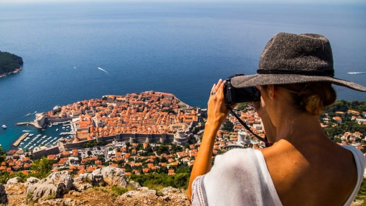 A woman wearing a hat looks into binoculars toward a red-tiled roofed town on the edge of the mediterranean ocean in croatia's dalmation coast
