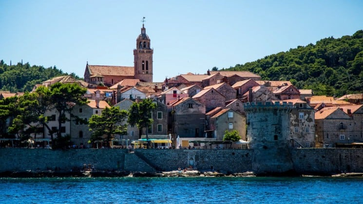 a town with a steeple and red-tiled roofs in croatia's dalmation coast as seen from the small ship callisto cruise