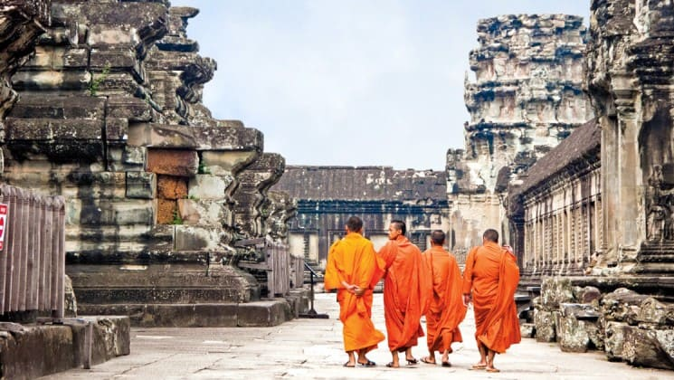 Four monks in orange robes walk through ankor wat's temples, a world heritage site in Southeast Asia