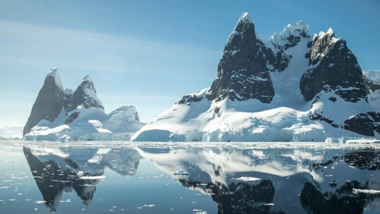 icebergs and jagged mountains are reflected in still water, as seen from crossing the antarctic circle cruise ship