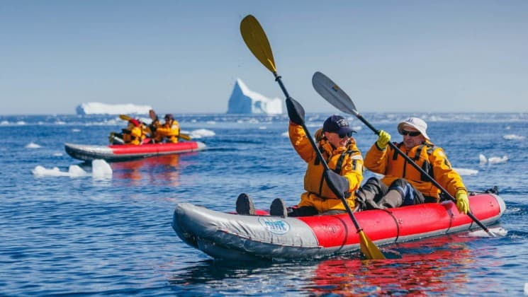 A couple paddles a sea kayak on the ocean with icebergs in the distance in antarctica