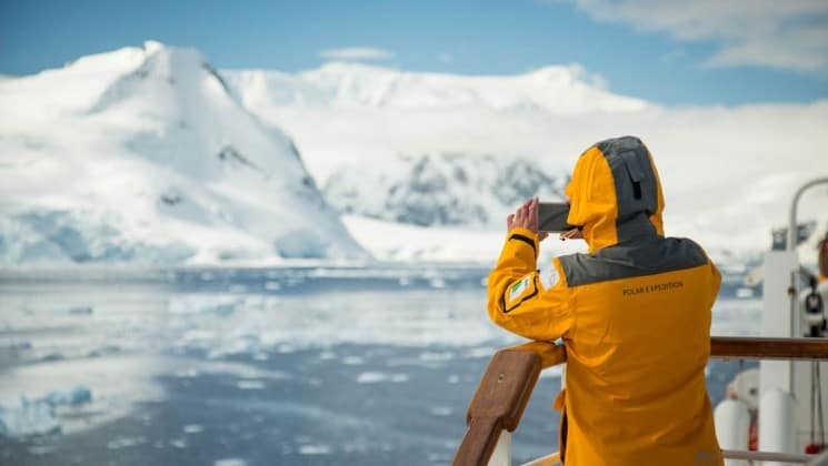A passenger aboard the explorers and kings expedition cruise takes a photo of the iceberg in the distance