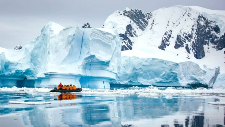 A zodiac boat with crossing the antarctic circle cruise ship carries passengers toward a gigantic iceberg floating in the ocean