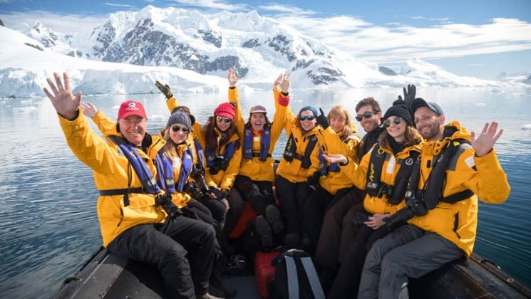 a group photo with passengers from the crossing the antarctic circle cruise ship pose on a zodiac boat headed toward the ice bergs