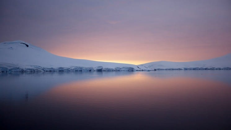 A landscape portrait of the horizon in Antarctica during sunset, with pink sky reflecting on the ocean and an iceberg
