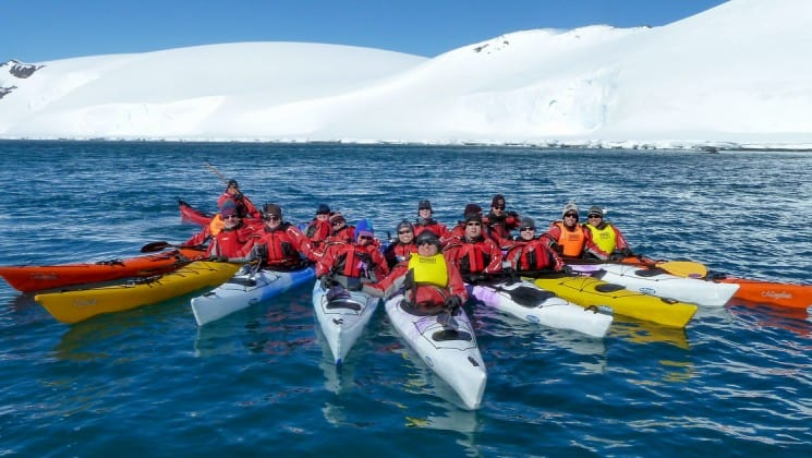 A group of kayaks pull up together in the antarctic peninsula with an iceberg in the background