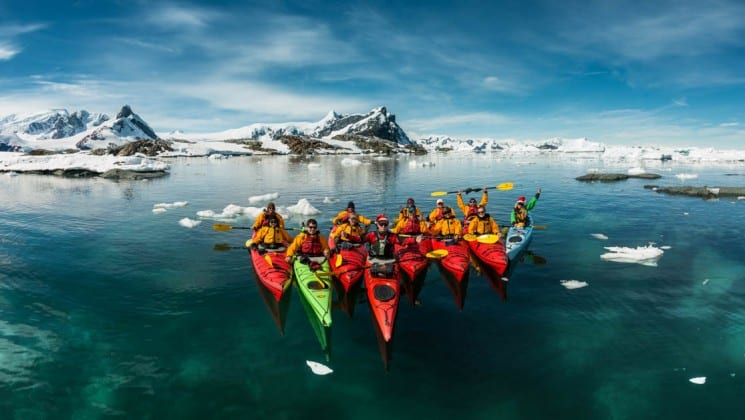 A group of sea kayaks pose in the ocean in front of icebergs in antarctica