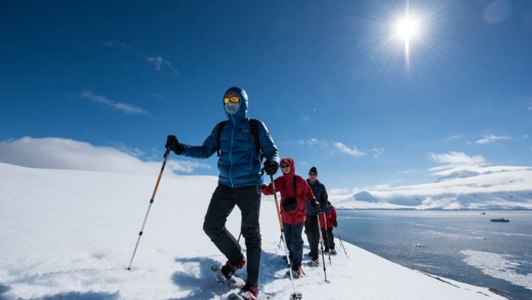 A group of hikers posthole in the snow up a mountain in antarctica